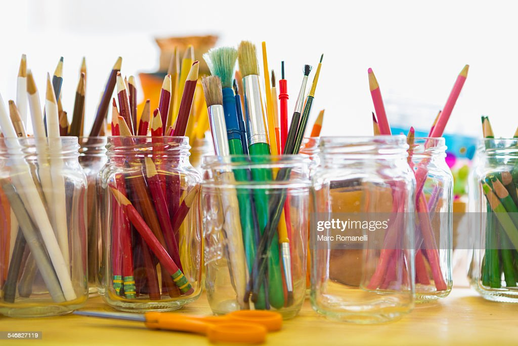 Close up of jars of colored pencils and paintbrushes : Stock Photo