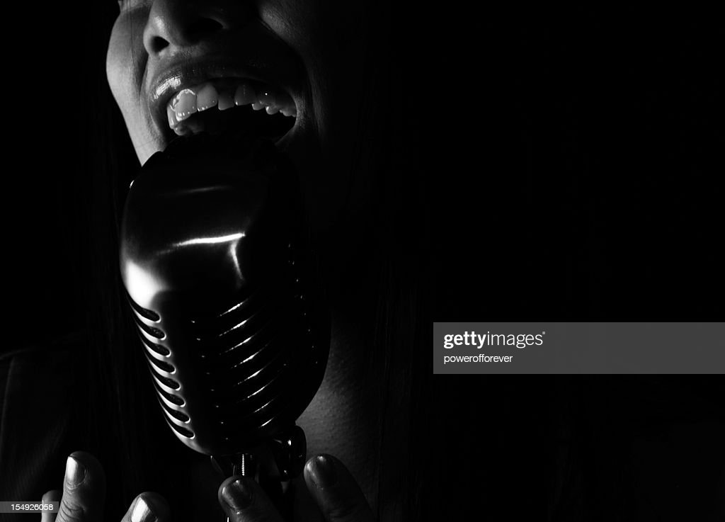 Close up of jazz Singer singing into a microphone : Stock Photo