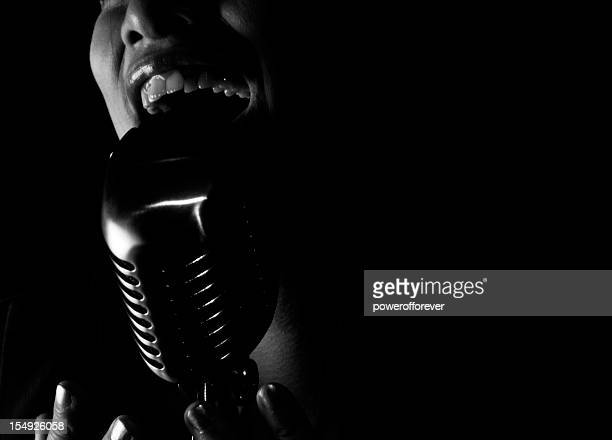 close up of jazz singer singing into a microphone - jazz stock pictures, royalty-free photos & images