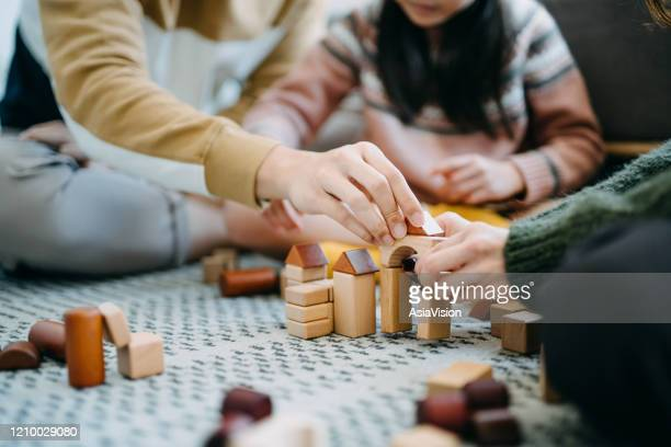 close up of joyful asian parents sitting on the floor in the living room having fun and playing wooden building blocks with daughter together - building blocks stock pictures, royalty-free photos & images