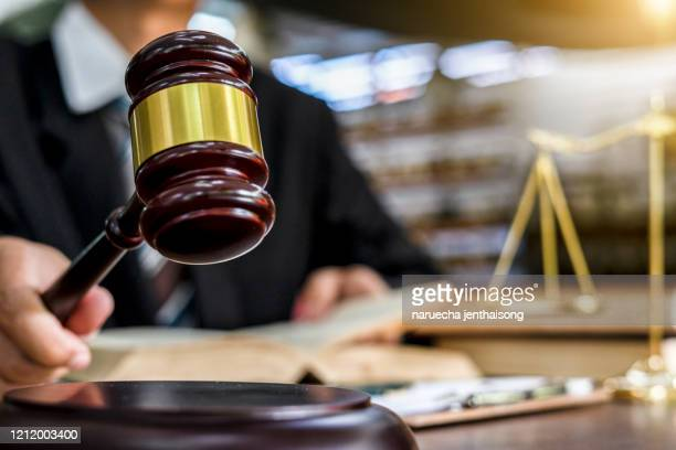 close up of judge holding gavel - courthouse stock pictures, royalty-free photos & images
