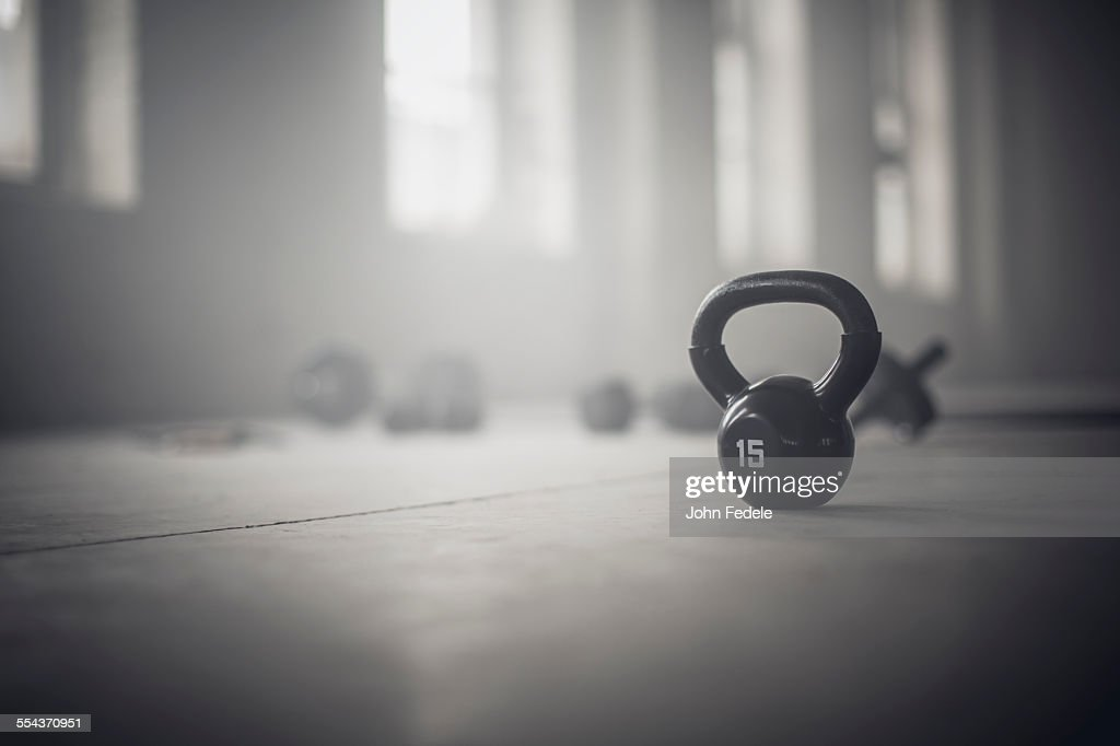 Close up of kettlebell weights on floor of dark gym : Stock Photo
