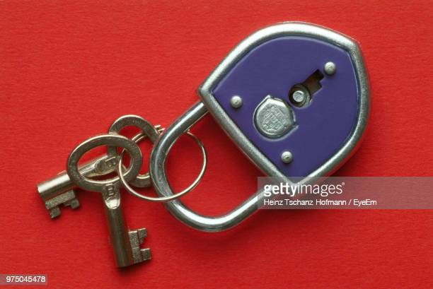 Close Up Of Key And Padlock Over Red Background