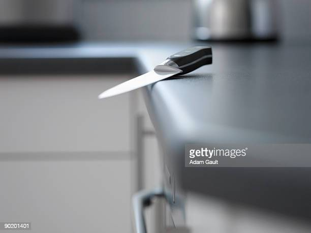Close up of kitchen knife about to fall off counter