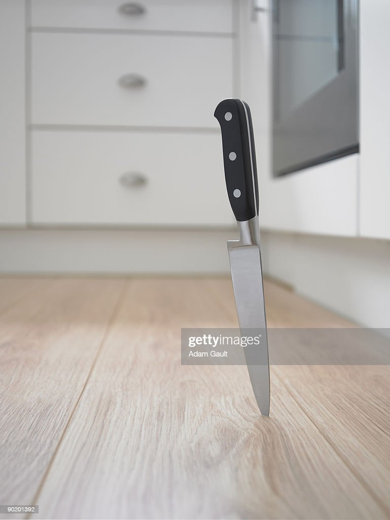 Close up of kitchen knife stuck in floor : Stock Photo