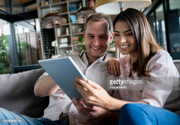 Close up of latin american couple at home relaxing on couch looking at social media on tablet
