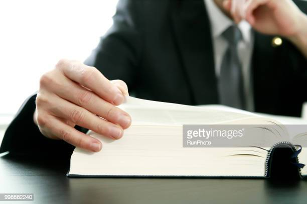 close up of lawyer reading law book at desk - 法 ストックフォトと画像