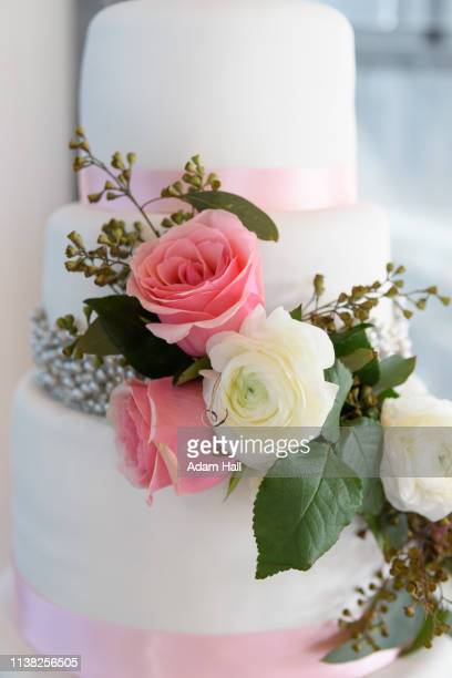 close up of layers of wedding cake with rose flowers, beads and ribbon - utah wedding stock pictures, royalty-free photos & images