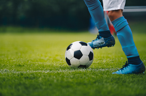 Close up of legs and feet of football player in blue socks and shoes running and dribbling with the ball. Soccer player running after the ball. Sports venue in the background 1150952747