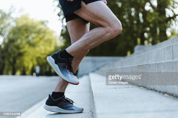 close up of legs of a sporty man training up on the stairs - muscular build stock pictures, royalty-free photos & images