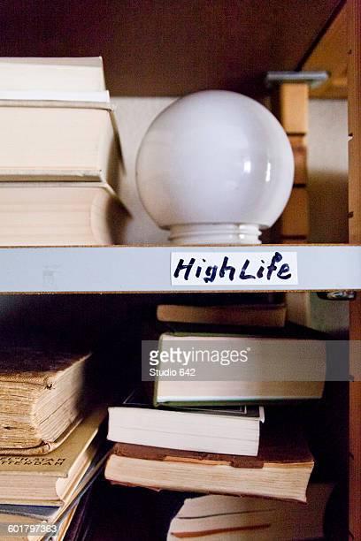 Close up of light bulb on shelf with books