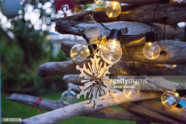 close up of light on creative  drift wood christmas tree - southern hemisphere stock photos and pictures
