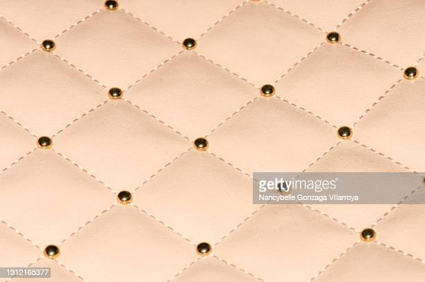 close up of light pink checkered faux leather with metallic studs - leather stock pictures, royalty-free photos & images