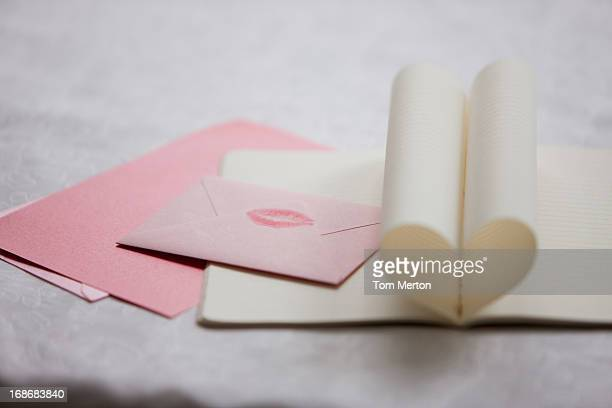 close up of lipstick kiss on envelope and pages of notebook forming heart-shape - love letter stock photos and pictures