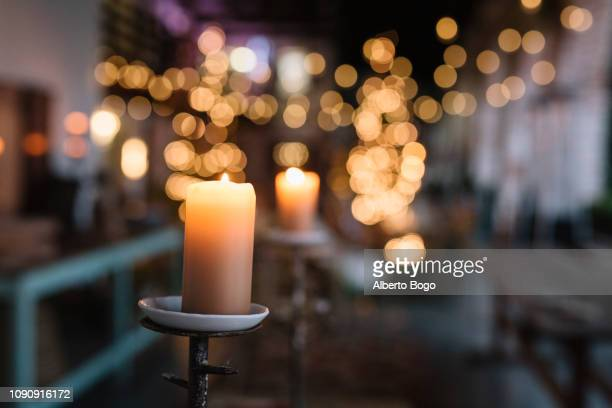 Close up of lit candle in cafe with decorative lights