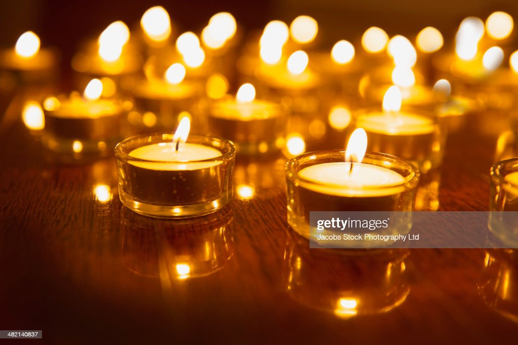 Close up of lit tea light candles on wooden table : Stock Photo