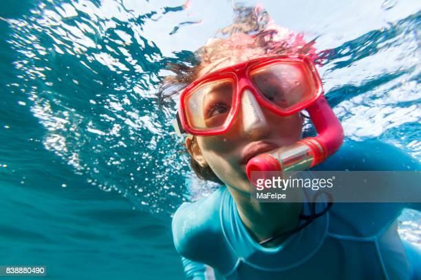 Närbild av liten flicka snorkling i Fernando de Noronha