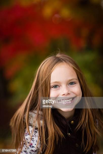 Gros plan de la petite fille debout à l'extérieur sur une journée d'automne