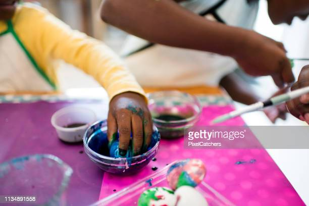 close up of little hands covered in food colouring painting easter eggs - african american easter stock photos and pictures
