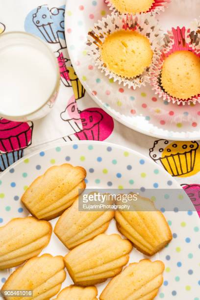 Close up of madeleines and cupcakes on polka dots pattern plates