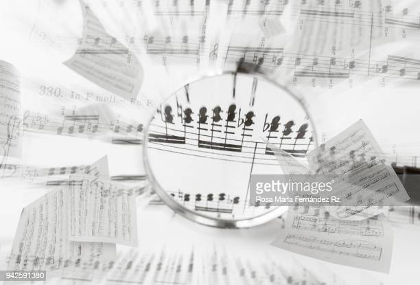 Close up of magnifying glass on blurred sheet music. Selective focus and copy space.