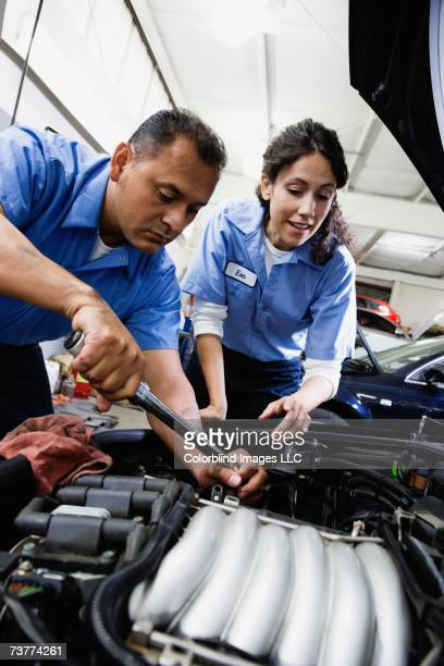 Close up of male and female auto mechanics working on engine in auto repair shop