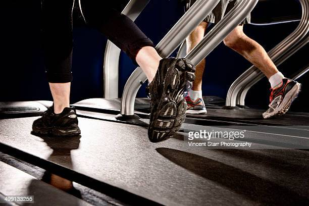 close up of male and female legs running on gym treadmill in altitude centre - scrutiny stock pictures, royalty-free photos & images