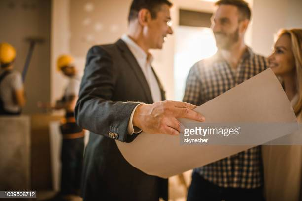 close up of male architect analyzing housing plan with a couple. - building contractor stock pictures, royalty-free photos & images