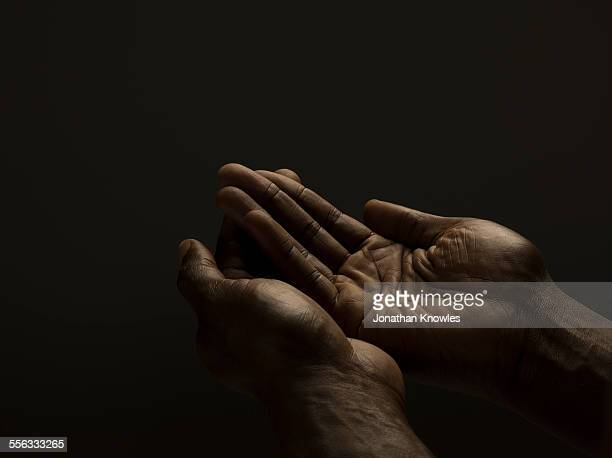 Close up of male cupped hands, dark skin