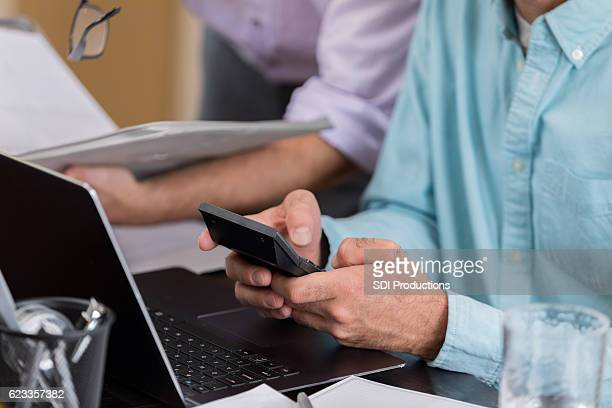 Close up of male entrepreneur using calculator and laptop