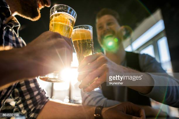 Close up of male friends toasting with beer in a cafe.