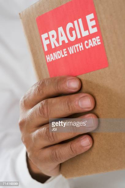 close up of male hand holding package with fragile sticker - fragile sticker stock pictures, royalty-free photos & images