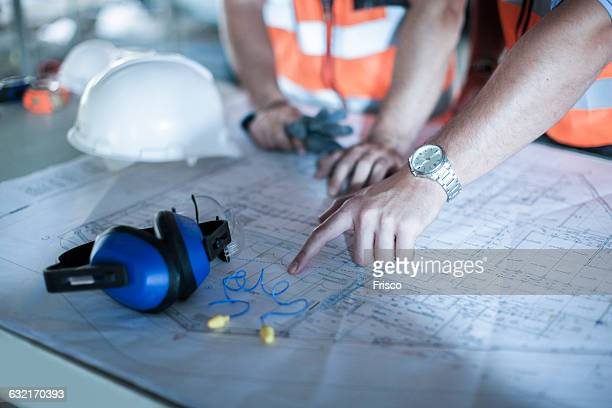 Close up of male hand pointing on blueprint in construction site