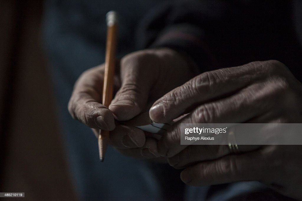 Close up of male hands holding a pencil and piece of wood : Stock Photo