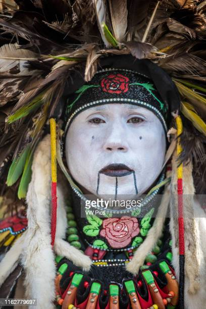 Close up of male Native American dancer belonging to the Lumbee tribe wearing a traditional costume and face paint Baltimore Maryland