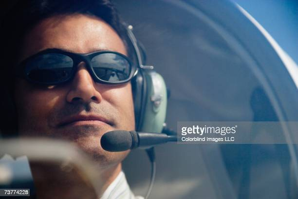 Close up of male pilot in cockpit of airplane