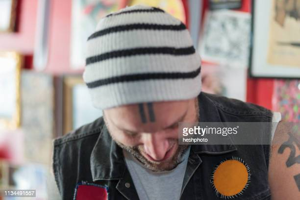 close up of male punk shop keeper smiling and looking down in vintage toy shop - heshphoto stockfoto's en -beelden