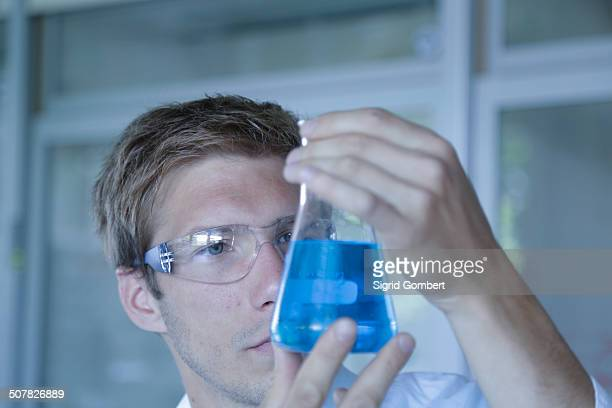 close up of male scientist holding up erlenmeyer flask in lab - sigrid gombert imagens e fotografias de stock