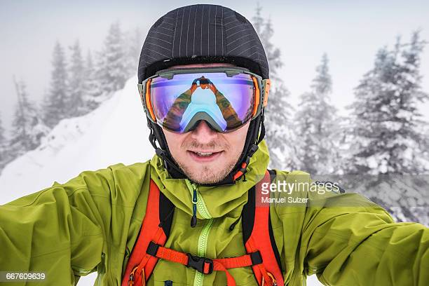 close up of male skier wearing ski goggles taking selfie on mountain at kranzegg, bavaria, germany - ski goggles stock pictures, royalty-free photos & images