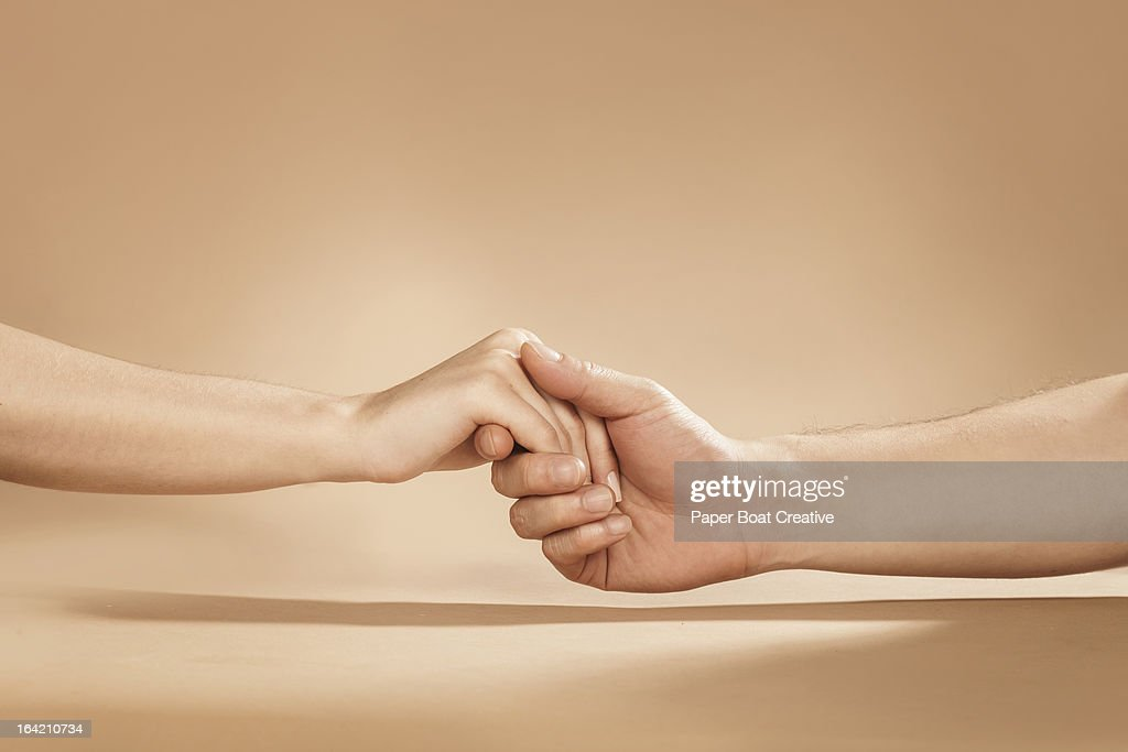 close up of man and woman holding hands in studio : Stock Photo