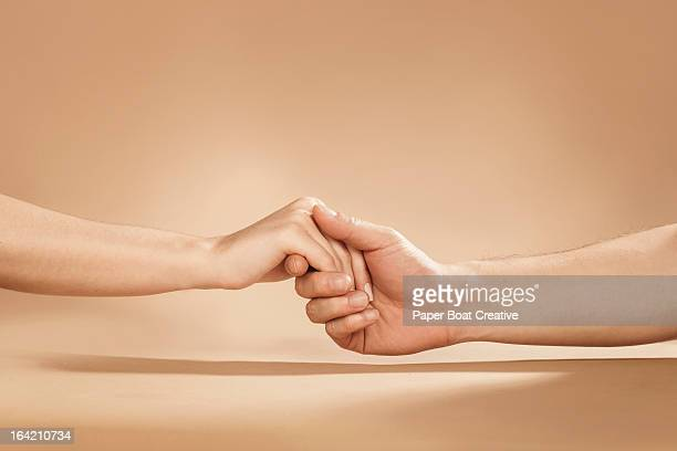 close up of man and woman holding hands in studio