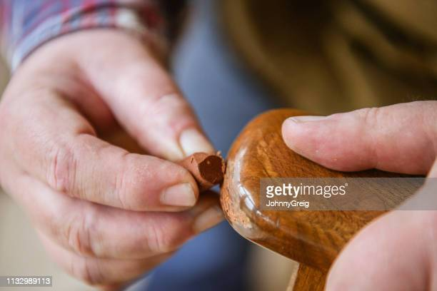 close up of man applying brown wax to chair arm - restoring stock pictures, royalty-free photos & images