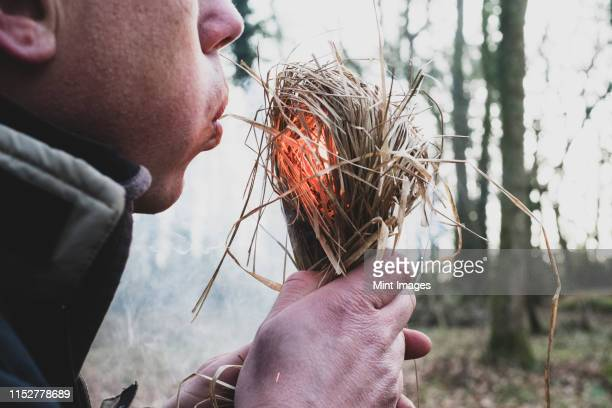 close up of man blowing on bundle of straw, igniting fire. - survival stock pictures, royalty-free photos & images