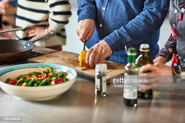close up of man chopping pepper on board with friends - vegetarian food stock pictures, royalty-free photos & images