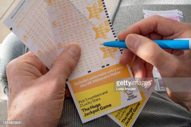 Close up of man filling in EuroMillions Lotto lottery form.