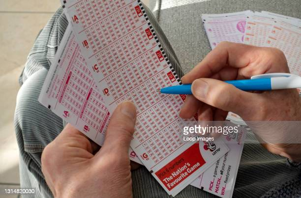 Close up of man filling in Lotto lottery slip.