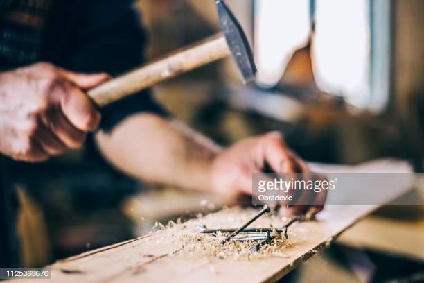 nahaufnahme des menschen hämmern einen nagel in holzbrett - hammer stock-fotos und bilder