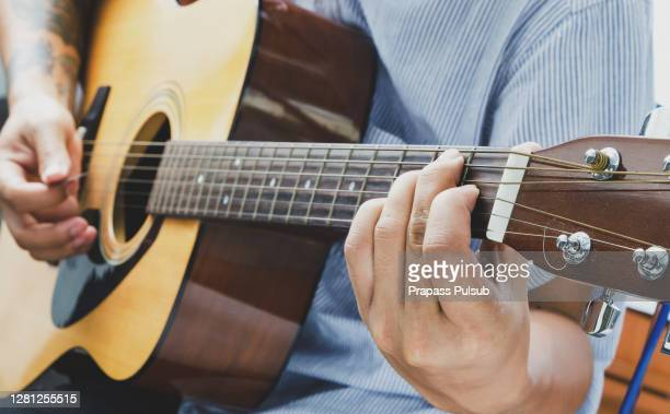 close up of man hand playing guitar. - acoustic music stock pictures, royalty-free photos & images