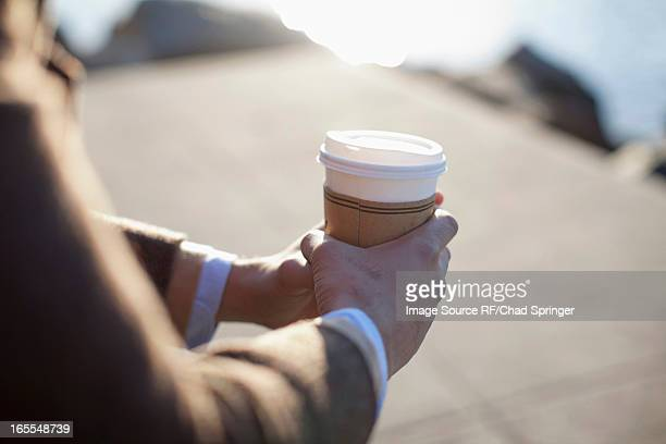 Close up of man holding cup of coffee