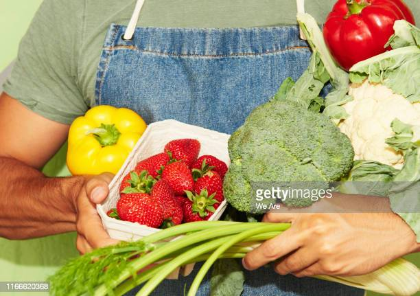 close up of man holding fresh vegetables - vegetarianism stock pictures, royalty-free photos & images